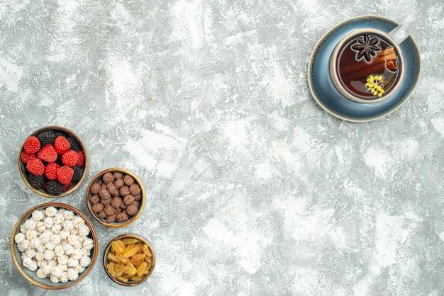 Vista dall'alto tazza di tè con diverse caramelle su uno spazio bianco