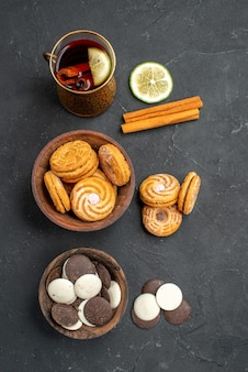 Top view cup of tea with different cookies on a dark surface