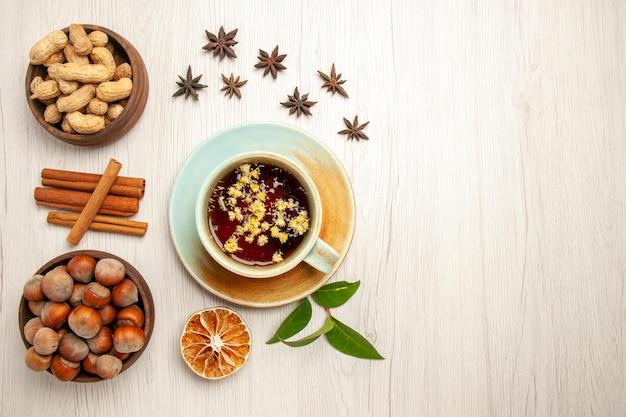 Vista dall'alto tazza di tè con noci diverse sulle noci di cerimonia della frutta del tè di colore bianco della scrivania