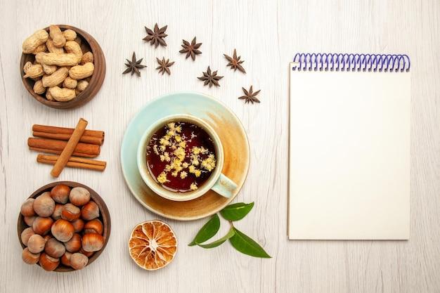Vista dall'alto tazza di tè con noci diverse sul dado di cerimonia della frutta del tè di colore della superficie bianca