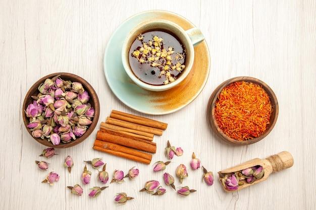 Vista dall'alto tazza di tè con fiori secchi e cannella sul fiore di colore del tè da scrivania bianco
