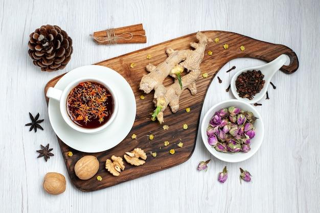 Vista dall'alto tazza di tè con fiori secchi e noci su sfondo bianco tè bevanda dado