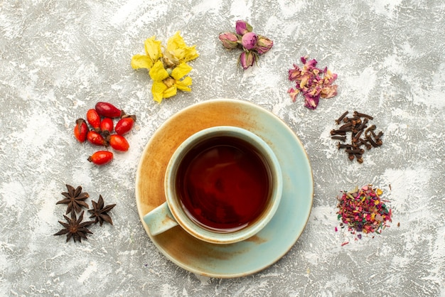 Top view cup of tea with dried flowers on white surface tea drink flower flavor