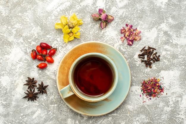 Vista dall'alto tazza di tè con fiori secchi su superficie bianca bevanda al tè sapore di fiori
