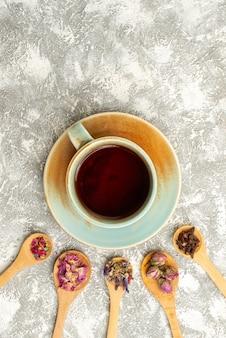 Vista dall'alto tazza di tè con fiori secchi sulla superficie bianca bevanda al gusto di fiori di tè