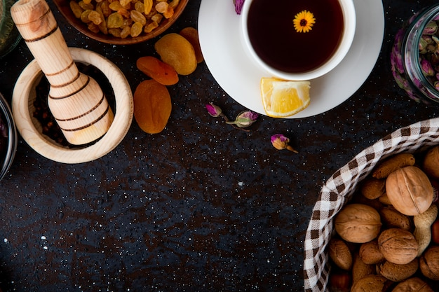 Top view of a cup of tea with dried fruits, walnuts and a wood mortar with black peppercorns on black with copy space