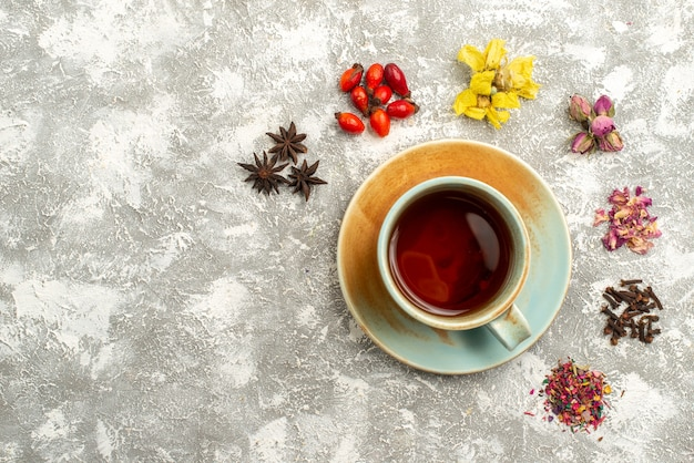 Top view cup of tea with dry flowers on white background tea drink flower flavor