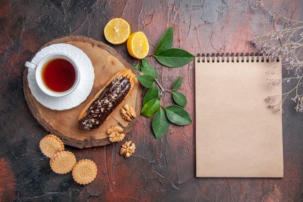 Vista dall'alto tazza di tè con eclair e biscotti sulla torta biscotto dolce tavolo scuro