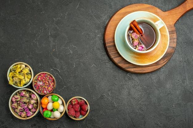 Vista dall'alto tazza di tè con fiori e caramelle sullo spazio grigio