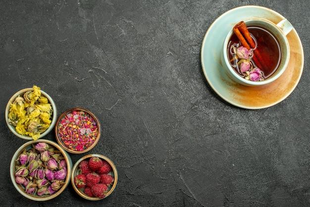 Vista dall'alto tazza di tè con fiori sullo sfondo grigio scuro cerimonia del colore della bevanda del tè