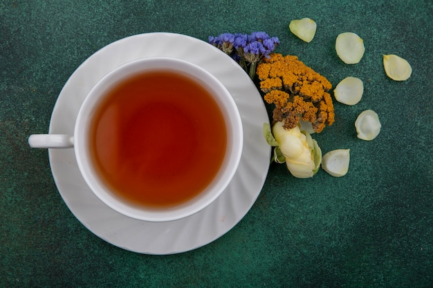 Top view cup of tea with flowers on green background