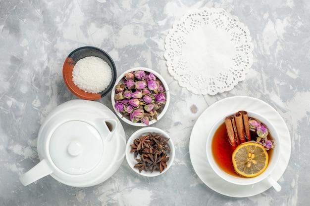 Vista dall'alto tazza di tè con fiori e bollitore sulla superficie bianca