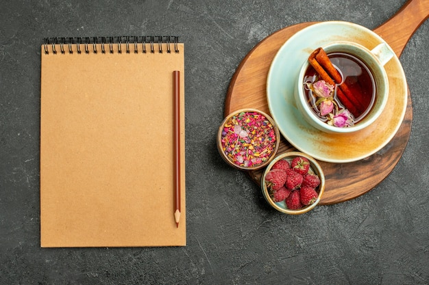 Top view cup of tea with flowers and notepad on grey background tea drink color ceremony flower