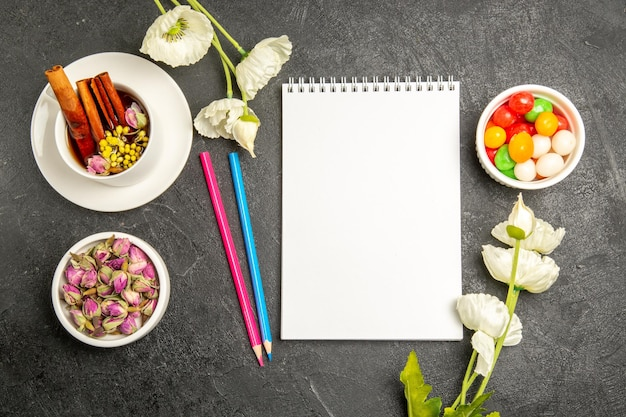 Top view cup of tea with flowers and pencils on a grey background tea drink color flower flavor