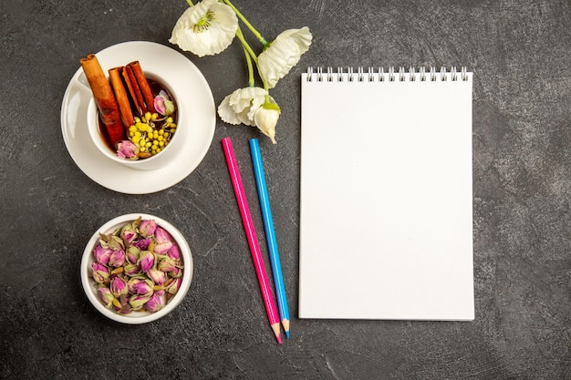 Top view cup of tea with flowers and pencils on grey background tea drink color flower flavor