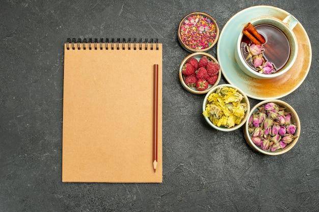 Vista dall'alto tazza di tè con fiori e lamponi sullo sfondo scuro tè bevanda alla frutta sapore flower