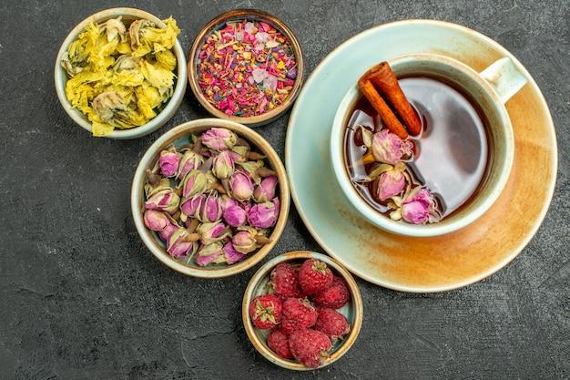 Vista dall'alto tazza di tè con fiori e lamponi su sfondo scuro i frutti del tè bevono il sapore del fiore