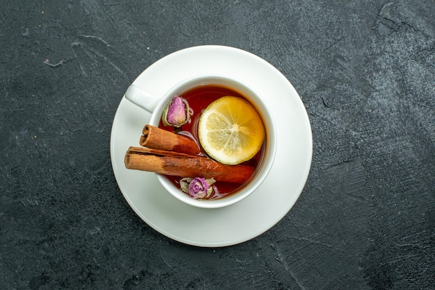 Top view cup of tea with flowers and tea on dark surface tea fruit citrus ceremony