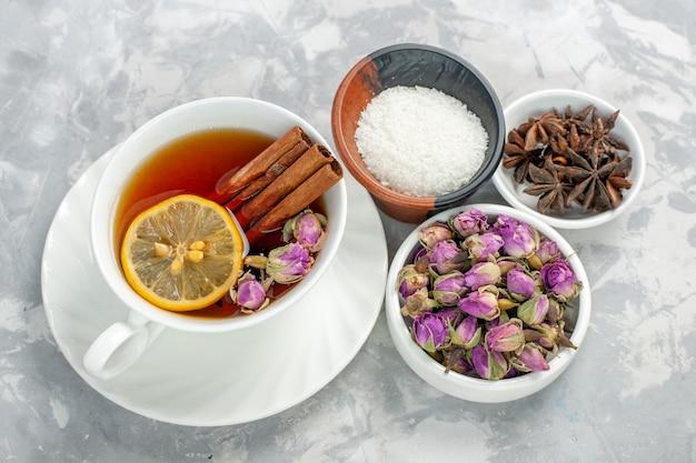 Vista dall'alto tazza di tè con fiori sulla superficie bianca