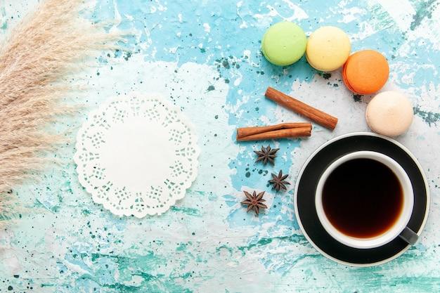 Tazza di tè vista dall'alto con macarons francesi sulla superficie blu