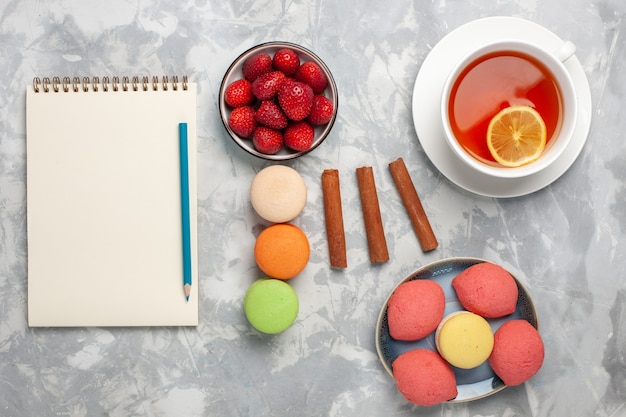 Vista dall'alto tazza di tè con macarons francesi e torte su superficie bianco chiaro