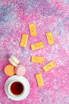 Top view cup of tea with french macarons and crackers on pink desk