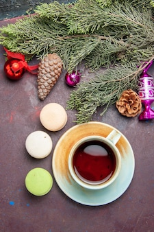 Top view cup of tea with french macarons on dark background cake biscuit sugar pie