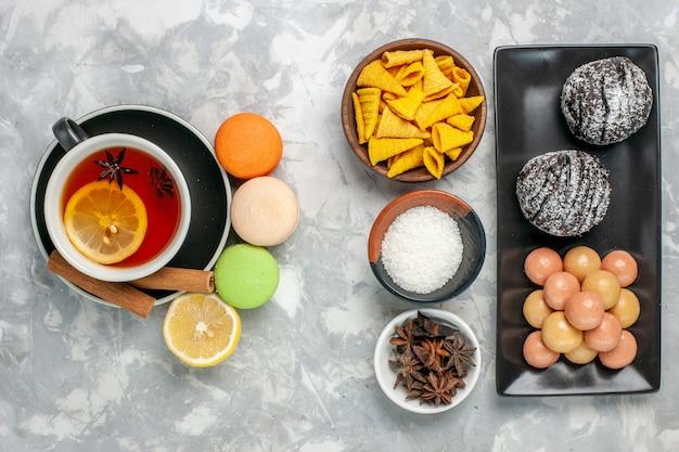 Vista dall'alto tazza di tè con macarons francesi e deliziose torte al cioccolato sulla superficie bianca