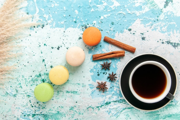 Tazza di tè vista dall'alto con macarons francesi sulla superficie azzurra