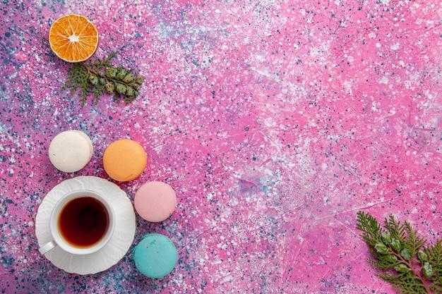 Vista dall'alto tazza di tè con macarons francesi sulla superficie rosa