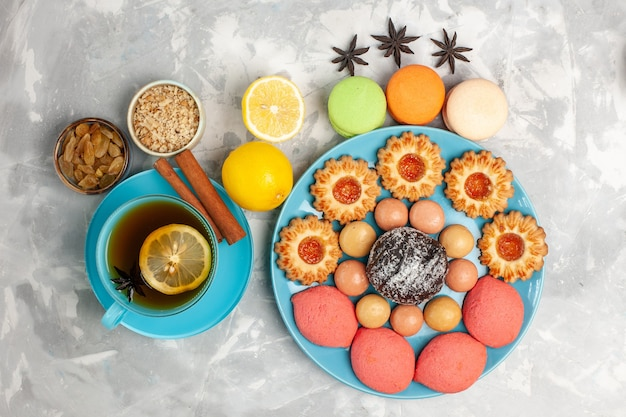 Top view cup of tea with french macarons sugar cookies and cakes on white surface