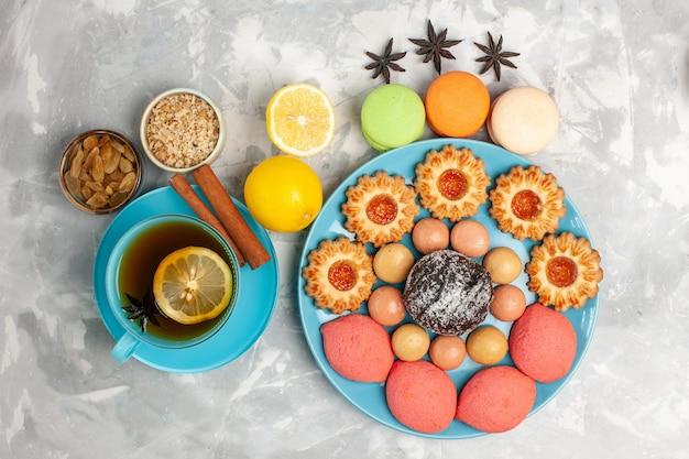 Vista dall'alto tazza di tè con biscotti di zucchero macarons francesi e torte su superficie bianca