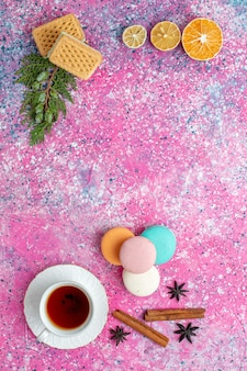 Top view cup of tea with french macarons waffles and crackers on light pink desk