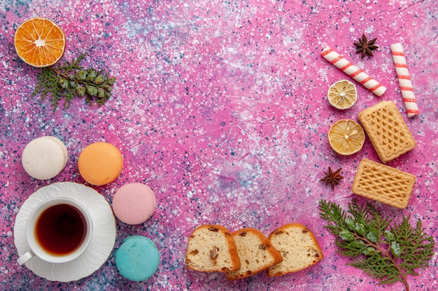 Top view cup of tea with french macarons and waffles on pink surface