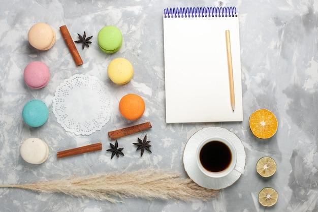 Vista dall'alto tazza di tè con macarons francesi su bianco