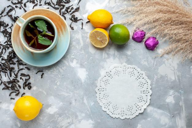 Vista dall'alto tazza di tè con caramelle di chicchi di tè essiccati freschi e limone sul tavolo luminoso, colazione da bere tè