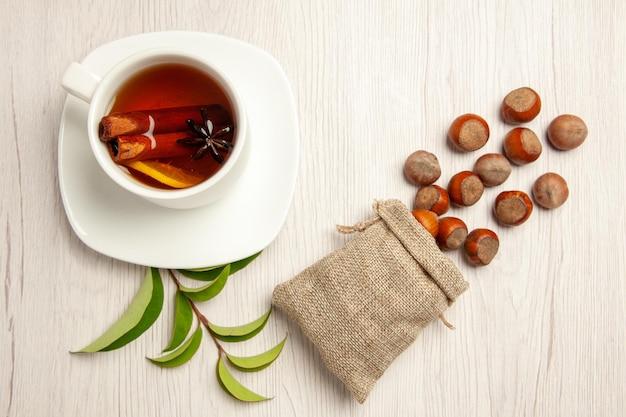 Vista dall'alto tazza di tè con nocciole fresche sulla cerimonia del tè con spuntino dado da scrivania bianco