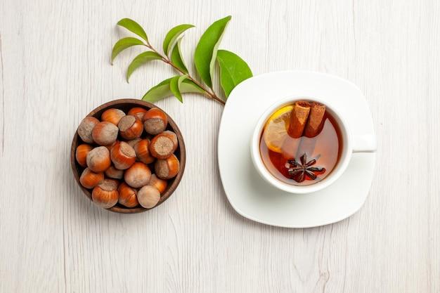 Vista dall'alto tazza di tè con nocciole fresche su cerimonia di spuntino con noce di tè da scrivania bianca