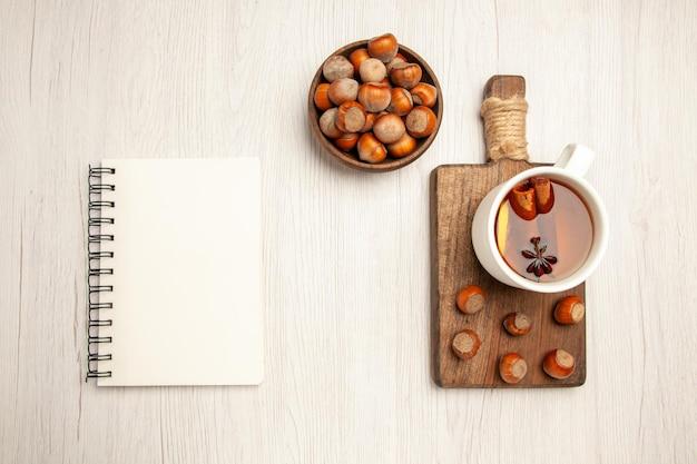 Vista dall'alto tazza di tè con nocciole fresche su scrivania bianca tè dadi cerimonia snack nocciola