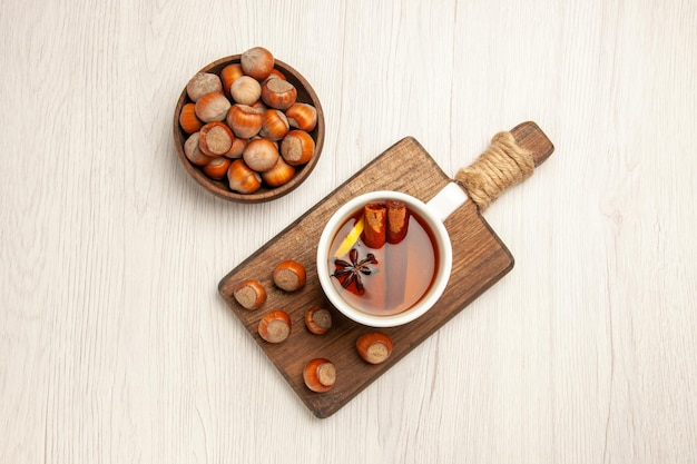 Top view cup of tea with fresh hazelnuts on white surface tea nut snack ceremony