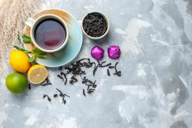 Vista dall'alto tazza di tè con limoni freschi caramelle e tè essiccato sul tavolo bianco, colore degli agrumi della frutta