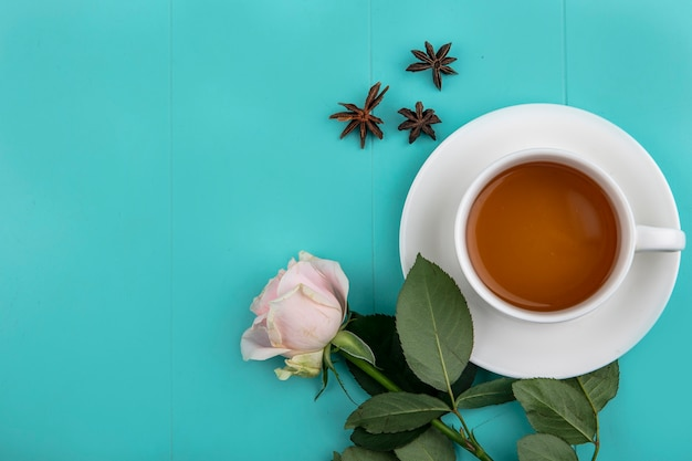 Top view of a cup of tea with fresh pink rose on a blue background with copy space