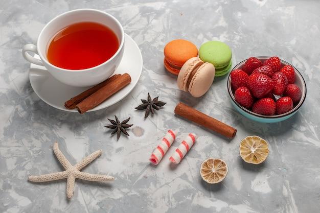 Vista dall'alto tazza di tè con fragole fresche e macarons francesi sulla scrivania bianca