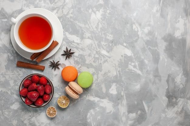 Vista dall'alto tazza di tè con fragole fresche e macarons francesi su superficie bianca