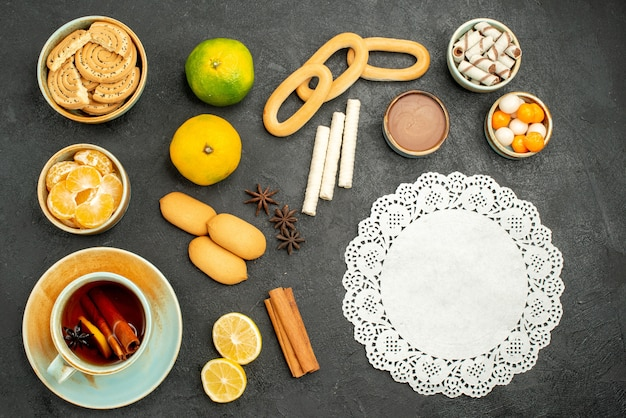 Top view cup of tea with fruits and biscuits on dark background