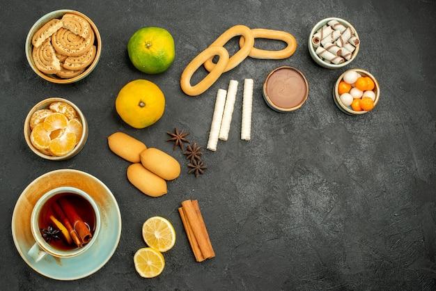 Vista dall'alto tazza di tè con frutta e biscotti sullo sfondo scuro