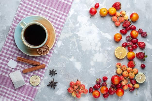 Vista dall'alto tazza di tè con frutta cannella su scrivania leggera frutta bacche fresche vitamina