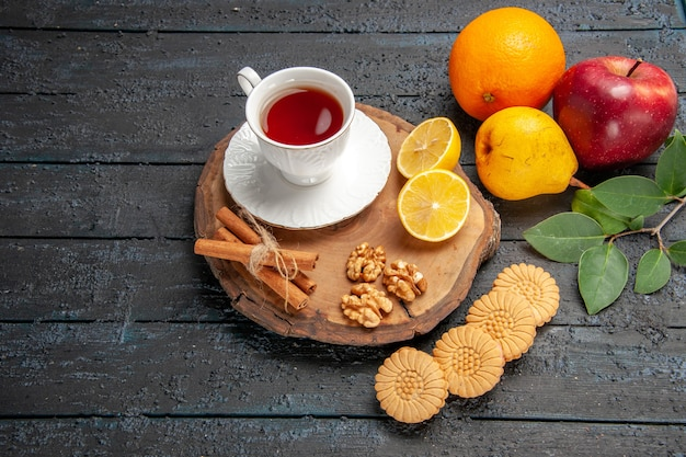 Top view cup of tea with fruits and cookies
