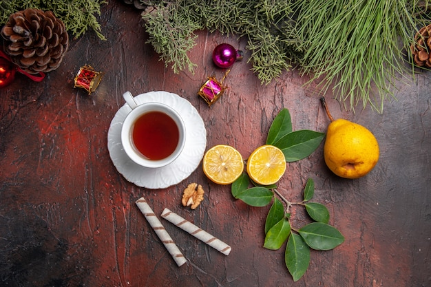 Top view cup of tea with fruits on dark table fruit tea photo dark