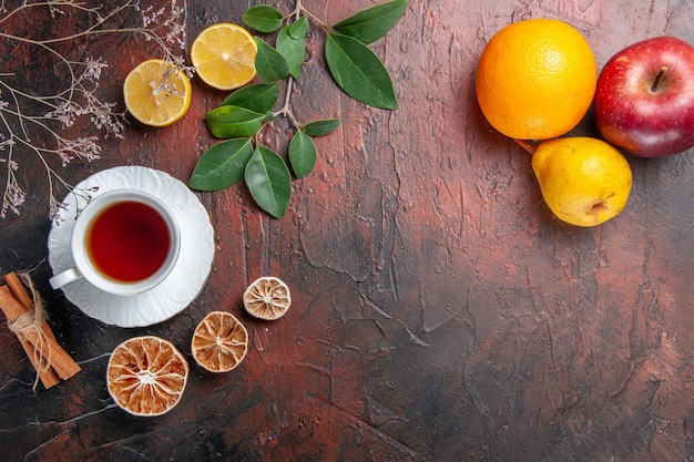 Top view cup of tea with fruits on dark table sugar tea photo biscuit sweet